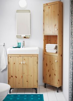 A small bathroom with a sink cabinet and a corner cabinet in light brown stained solid pine