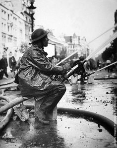 Photo: A fireman attempts to check the flames from a gas explosion, after an air raid in Central London the previous night. (Photo by Central Press/Getty Images). 1940