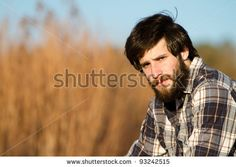 Young Man - This is a portrait of a young man with a beard sitting out side on a sunny day. by RONORMANJR, via Shutterstock