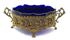 A French Neoclassical Style Gilt Metal Center Bowl,  of oval, handled form, fitted with a cobalt glass liner.