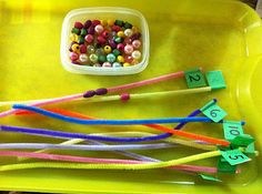 Putting the right amount of beads on numbered pipe cleaners.