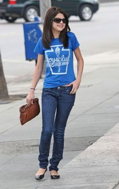 Selena Gomez wearing jeans and a graphic tee while walking around