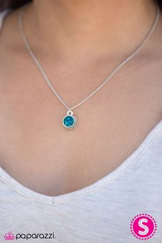 A sparkling blue gem is nestled inside a textured silver frame, creating a simple, yet colorful pendant. Features an adjustable clasp closure.   Sold as one individual necklace. Includes one pair of matching earrings.