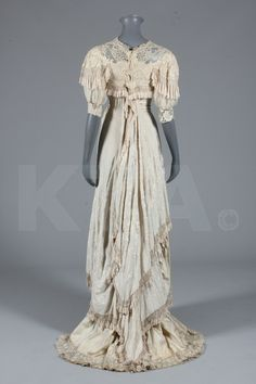 A bridal gown of Cantonese embroidered silk, circa 1910, with chiffon puff sleeves, lavishly embroidered swathed silk over-dress trimmed with fringes and tassels, chemical lace trim to hem, bust approx 92cm, 36in