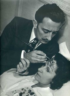 Salvador Dali painting on a woman's head.