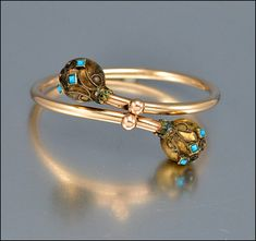 Victorian Gold Bangle Bracelet, 1880s Bypass. Victorian gold filled bangle bracelet with Etruscan design ends and turquoise stones. The bypass style bracelet has large balls at each end with diamond shaped turquoise stones set in an Etruscan design. Via boylerpf