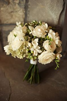 White bridal bouquet featuring with roses, freesia, blackberries and hydrangeas