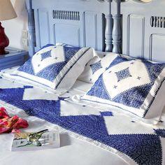 des draps brodés en bleu avec des motifs géométriques inspirés du Maroc