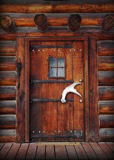 Shed antler shed handle on log cabin.