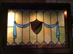Antique shield and drape stained glass window