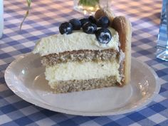 lemon mousse cake with hazelnut genoise layers drizzled with lemon syrup and topped with blueberries