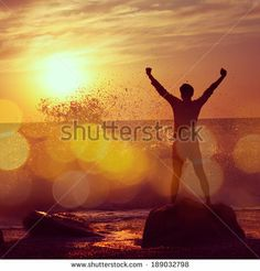 Silhouette of Man with Raised Arms at Stormy Sea. Freedom Concept. Instagram Styled Filtered Photo with Bokeh. - stock photo