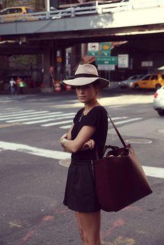 all black + wide-brimmed fedora + big leather bag + cuff