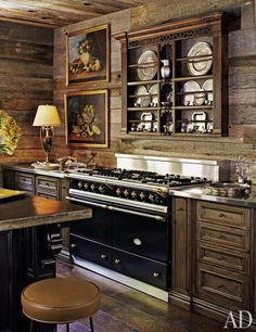 Architectural Digest ~The walls and ceiling in the kitchen of a log cabin–style home in the foothills of Tennessee's Great Smoky Mountains are clad with salvaged wood. Interior designer Suzanne Kasler decorated the space with a pair of 18th-century French still lifes and a 19th-century English-oak rack.