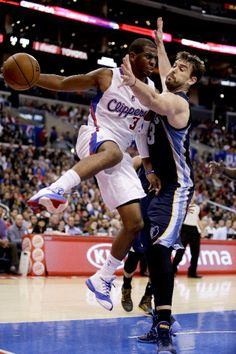 Los Angeles Clippers guard Chris Paul, left, passes around Memphis Grizzlies center Marc Gasol