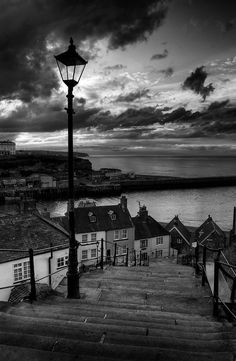 After rain filled grey skies during a wet day in Whitby North Yorkshire, the storm clouds part to reveal an incredible sunset. Tendrils of colour mix with the blue and greys of fast moving sky. Waves bow under pier and sand. The 199 steps leading up to Whiby Abbey create a pathway to Summers past.
