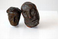 Ein größerer Tonkopf, der ein äteres,männliches Gesicht mit etwas verschobenen Gesichtszügen zeigt, ist an ein kleineres,  junges, männliches Gesicht hat,  angelehnt.