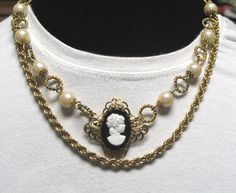 Summer Necklace: Faux Pearl & Goldtone Link Necklace with a Black and White Cameo on Filigree. $75 on Etsy. I also show it worn with an extra goldtone chain, and a string of pearls (neither of these are included). https://www.etsy.com/listing/202008048/faux-pearl-goldtone-link-necklace-with-a?ref=shop_home_active_1