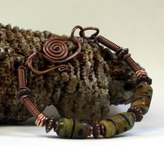 The beautiful Earth Bead Lampwork Bracelet is hand created with copper wire, coiled copper wire, 3 beautiful etched lampwork beads in shades of tan, black, rust, and blue greens, copper accent beads, a hand created forged clasp. Fits up to a 7 1/2 inch wrist, jump rings can be added to make it fit a larger wrist. This will be a gorgeous handcrafted bracelet to add to your jewelry collection.