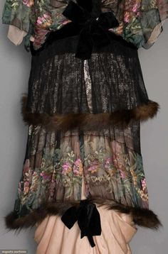 PRINTED LAME EVENING GOWN, c. 1913. Gown of floral printed & lame brocaded chiffon w/ black lace, short kimono sleeves, 2 fur trimmed chiffon & lace skirt tiers, black velvet bow trims, narrow draped pale pink underskirt Detail