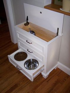 *****Made from small dresser. Pet food is kept in top with a scoop. Drawers hold all pet supplies, leash, collar, sprays, etc. with bowls integrated in the bottom drawer. Clever! **********