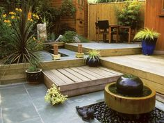 A tiered design can add dimension to a petite patio, as well as defining areas for seating, dining and other uses. Here, a mix of wood and slate, married with plant materials of contrasting color but similar tones, creates four levels of interest in this small space.