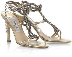 Jimmy Choo Toga jeweled sandals: Gold leather jeweled sandals, approximately 100mm high. Jimmy Choo sandals have a hook fastening around ankle and heavy jeweled design along the foot with thin gold straps to the side.
