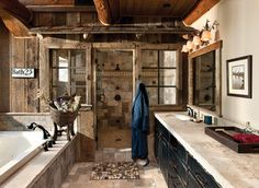 Weathered wood panels and barn-style additions, make this master bathroom's appearance simulate an old western outhouse.Photo Cred: Heidi Long, Longview