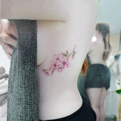 Cherry blossom tattoo on the left side ribcage.