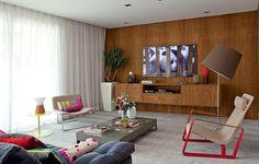 A TV deste apartamento foi apoiada em um painel de imbuia, assim como o móvel suspenso abaixo dela. A grande quantidade de madeira usada neste projeto da designer de interiores Magda Marconi deixou o ambiente aconchegante
