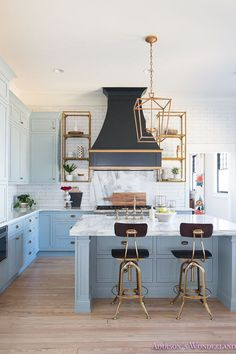 Blue Kitchen with Brass accents. A black French kitchen hood, painted in Sherwin Williams Inkwell, is accented with gold trim and it's flanked by brass shelving. Blue kitchen features blue shaker cabinets painted in a custom color, 50% of Sherwin Williams Stardew and 50% Uncertain Gray, paired with Calcutta Reale Marble countertops and a linear white tile backsplash. A black French kitchen hood painted Sherwin Williams Inkwell is accented with gold trim, flanked by brass shelving units…
