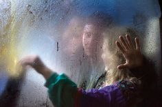 A couple sitting my a frosted window of a night bus in London, shot by photographer Nick Turpin