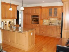 Helen Richardson designed this traditional kitchen with warm wood cabinets and a neutral backplash and countertops.