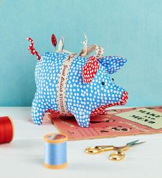 In patriotic red, white and blue, with a sweet curly tail and a ribbon bow, our little Sewing Bee piggy pincushion will make a handsome addition to your workspace.