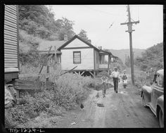 6. Coal mines often set up small towns or camps for its workers, including houses, schools and a company store. However, many did not offer the best accommodations. In this photograph, also of the Kingston Pocahontas Coal Company,  a miner and his children walk home with groceries along an unpaved road without sidewalks and no apparent camp maintenance. .