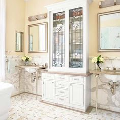 This bathroom is in an 1880s San Francisco Queen Anne house featured on BHG.com. I love the center cabinet, which was built to fit salvaged, 100-year-old beveled leaded glass doors.