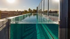 Lap pool with acrylic window constructed on the side of a three storey house. Pinned to Pool Design by Darin Bradbury.