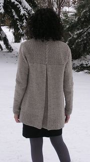 This cardigan features long, lean lines, and a dramatic center-back pleat. The body is worked in one piece from bottom up to the armholes. The pleat is knitted in and bound-off. Separate pieces are worked for the back yoke, collar, and sleeves. The sleeves are knit in the round and sewn into the armhole.