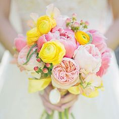 Pink and Yellow Bouquet Kate's spring bouquet included coral charm peonies, Campenella and Juliet garden roses, yellow ranunculus, veronica, sweet peas, tulips, and pink hypericum berries.   SouthernWeddings.com: Sweet Spring Serenbe Wedding Photo: Gracie Blue Florist: Holly Bryan Floral & Botanical Design