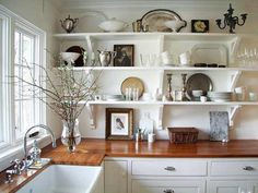Design Ideas for Kitchen Shelving and Racks: Combine function with decorative flair. The open shelving in this cottage-style kitchen provides a roomy expanse of storage, but it's also an opportunity to enhance the decor. Vintage pewter, china and other dishware mingle with practical supplies such as plates and glasses. The openness of the shelves also helps to preserve the serene, airy feel of the space and lends an old-fashioned note, evoking an era when most kitchens featured utilitaria…