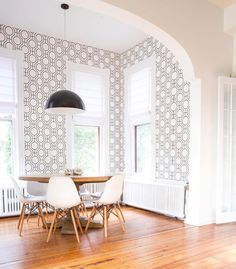 Monochromatic and mid-century modern dining room with geometric wallpaper