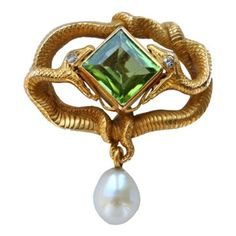 KARL ROTHMÜLLER An Eternal Entwined Serpent Brooch - KARL ROTHMÜLLER An Eternal Entwined Serpent Brooch Germany circa 1900 The naturalistic serpents biting a large emerald cut fine green peridot. The power & vitality of a good Lalique jewel.
