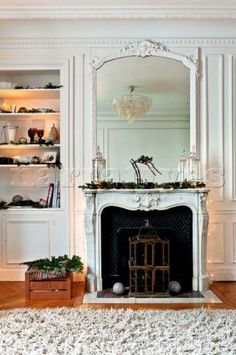 Mirror on marble fireplace with birdcage and recessed shelving at Christmas  in Paris apartment