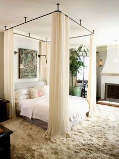 light grey upholstered bed and curtains around the bed to make it comfy and private