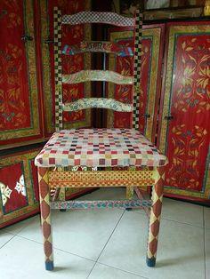 Silla lijada y pitada a mano con acrílicos y algunos motivos con papel y pegamento. Encima del asiento lleva una tapicería movible para facilitar el