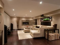Family room w/ sectional sofa - subwoofer speakers hidden behind the 120in screen, and projector concealed in ceiling niche; fireplace, surrounded by terracotta ledgestone, adds warmth and a romantic vibe