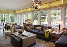 This contemporary sunroom features updated furniture and bright pops of color plus a great view of the outdoors.