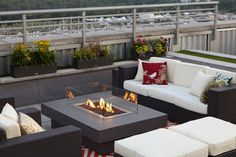 Contemporary chairs, stools and a sofa surround a modern fire pit on this rooftop deck. Patterned pillows add a pop of color to the neutral furniture.