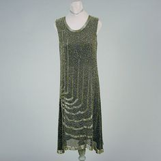 Beaded Black Chiffon Chemise Dress  Belgian, mid 1920s   Straight line, sleeveless, with the skirt flaring from hip level, the hem scalloped and dipping lower at each side, of fine stiff gauze sewn allover with clear seed beads and decorated with a concentric pattern emanating from right hip upward in vertical lines to neckline and downward across skirt in scalloped pattern, similar beading at hem, size 6, labeled: Hand Made In Belgium and handwritten number.