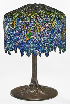 """TIFFANY STUDIOS """"Wisteria"""" Table Lamp Estimate $700,000 - $900,000 27 in. (68.6 cm) high<br />18 5/8  in. (47.3 cm) diameter of shade leaded glass and patinated bronze"""